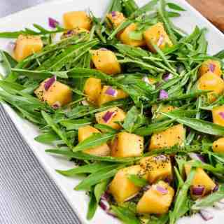 Cantaloupe Arugula Salad on a white platter