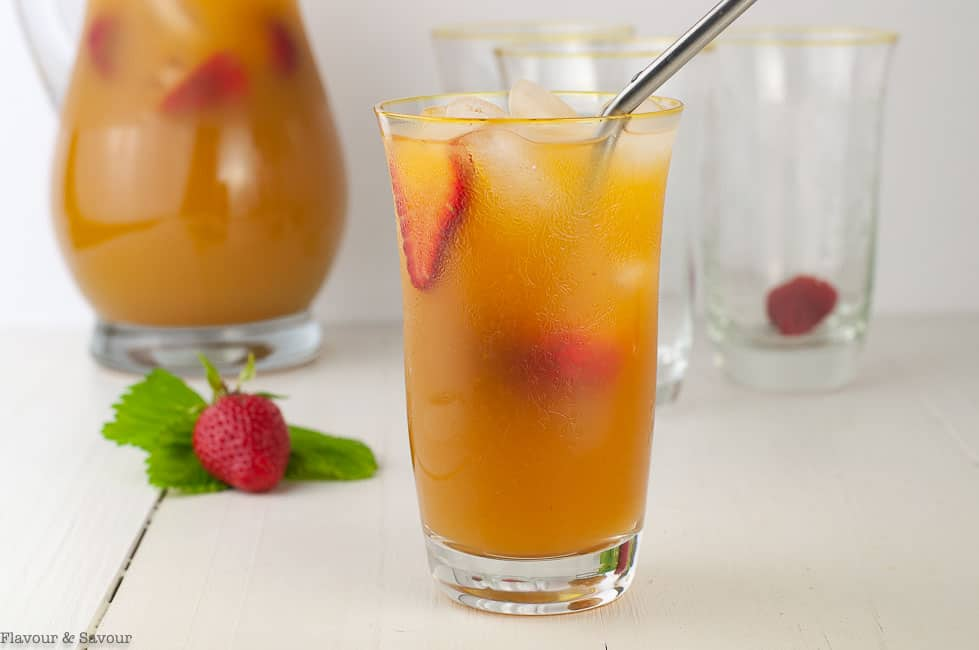 Peach Ginger Iced Tea in a glass with a stainless steel straw