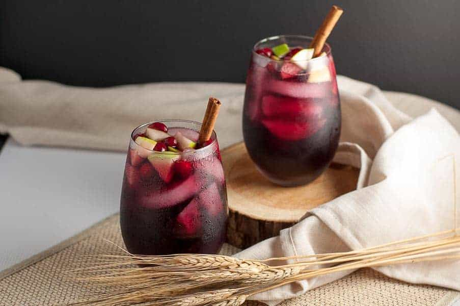Super simple Cranberry Apple Cider Sangria garnished with cranberries, apples and a cinnamon stick
