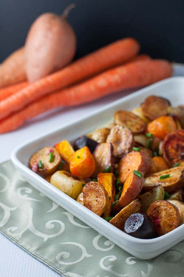 Crispy Apple Cider Roasted Root Vegetables in a serving dish with carrots in the background