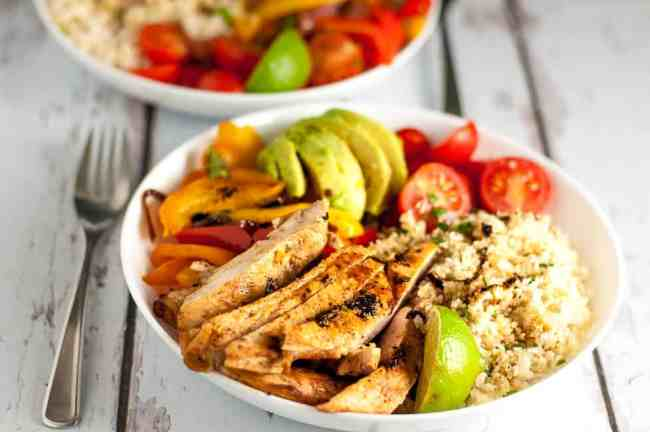 Chicken Fajita Bowl with Cauliflower Rice. A paleo meal-in-a-bowl. Succulent, juicy chicken, peppers, avocado, tomatoes and cauliflower rice, with a squeeze of lime!  www.flavourandsavour.com