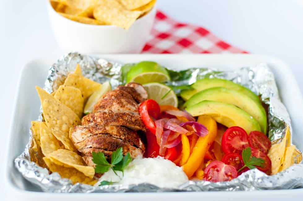 Easy Chicken Fajitas in Foil Packets garnished with peppers, avocado, tomatoes, lime and tortilla chips