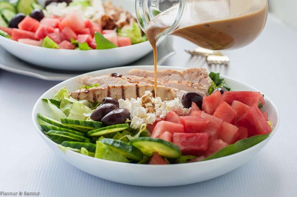 Adding dressing to Skinny Greek Chicken Bowl with Watermelon and Feta