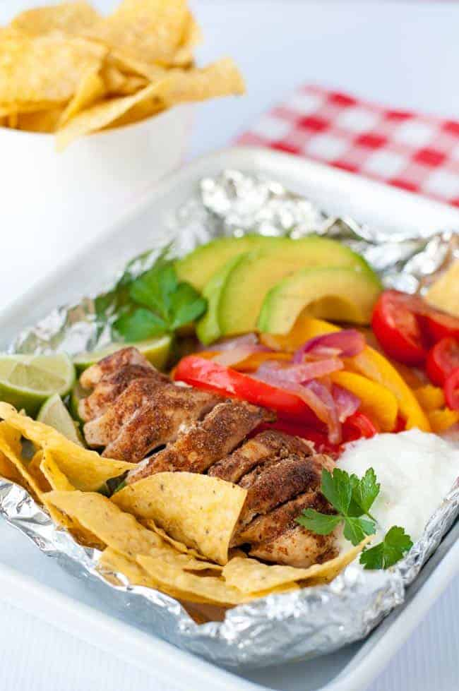 Easy Chicken Fajitas in Foil Packets with bell peppers, avocado, tomatoes and tortilla chips.