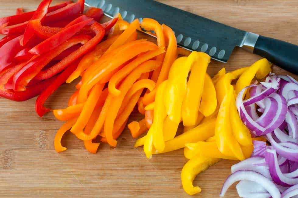 Slicing tri-coloured peppers and red onions for Easy Chicken Fajitas in Foil Packets