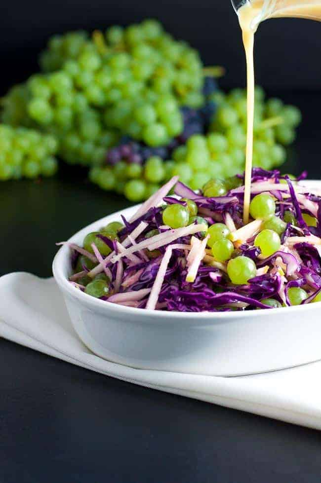 Grape, Apple and Red Cabbage Slaw. It's crunchy, tart and sweet, all at the same time and it's dressed with a light apple cider and honey vinaigrette that adds just the touch of sweetness needed to perfectly balance the flavours.  www.flavourandsavour.com