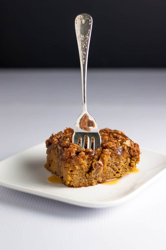 A square of Paleo Pumpkin Pecan Caramel Coffee Cake with a fork sticking into it