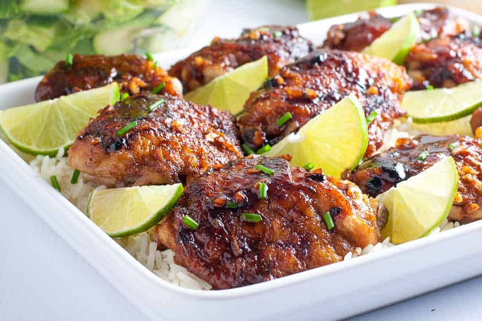 Honey Lime Chicken Thighs on a platter with lime slices.