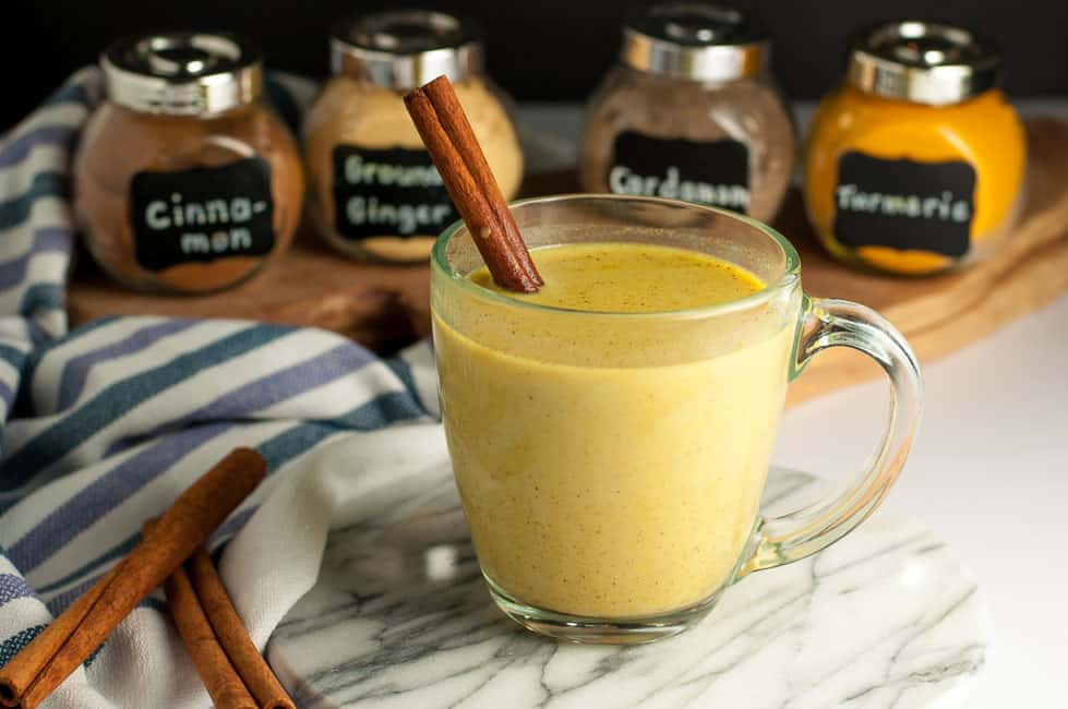 Warm Turmeric Cinnamon Milk with spice jars in background