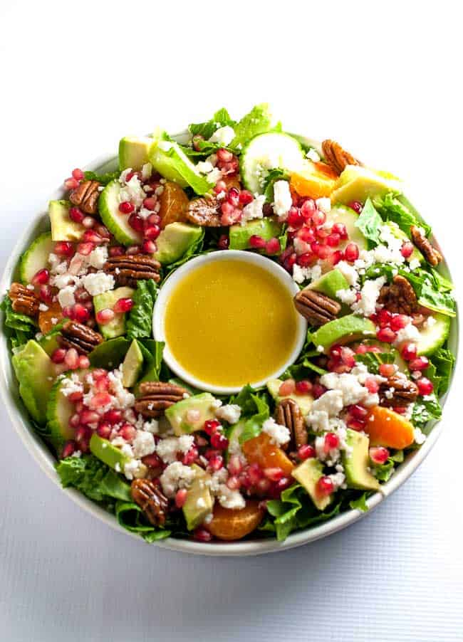 Pomegranate Mandarin Salad with Avocado and Feta in a wreath shape with dressing in a bowl in the center.
