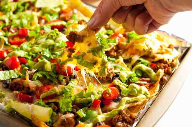 Loaded Sheet Pan Nachos with Black Beans and Avocado Cream.