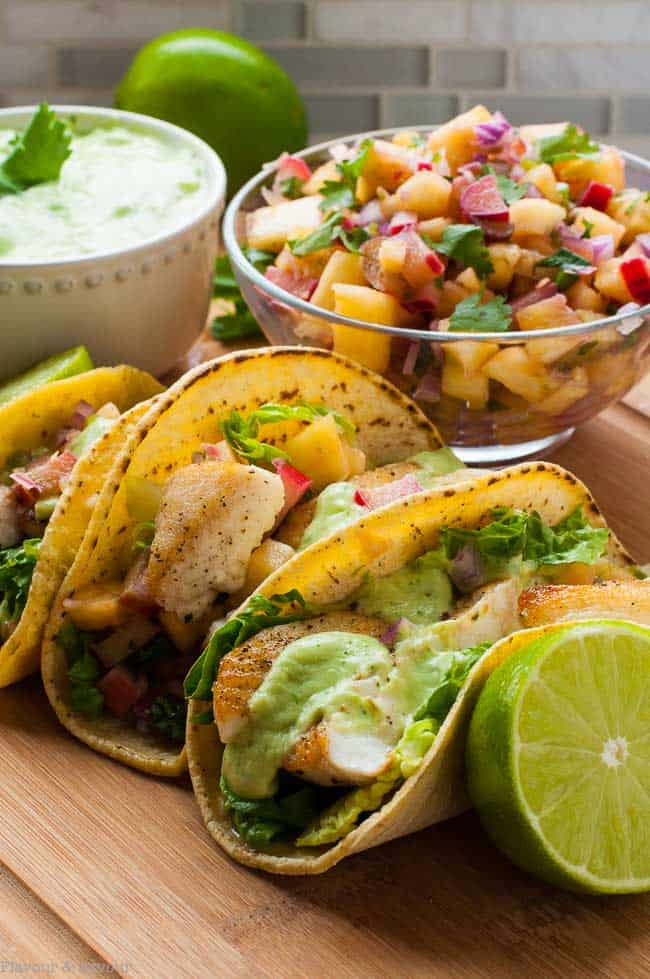 These Grilled Fish Tacos with Pineapple Rhubarb Salsa are stuffed with salt and pepper crusted fish, a piquant fruit salsa and they're topped with a creamy avocado dip.