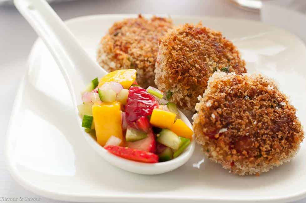 Tex-Mex Crab Cakes with Strawberry Mango Salsa on a white plate with a spoonful of colourful mango salsa