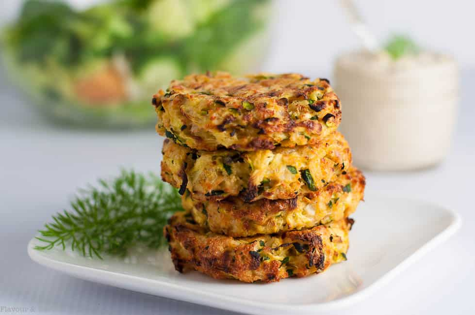 Crispy Baked Zucchini Patties stacked on a plate with lemon tahini dip in the background.