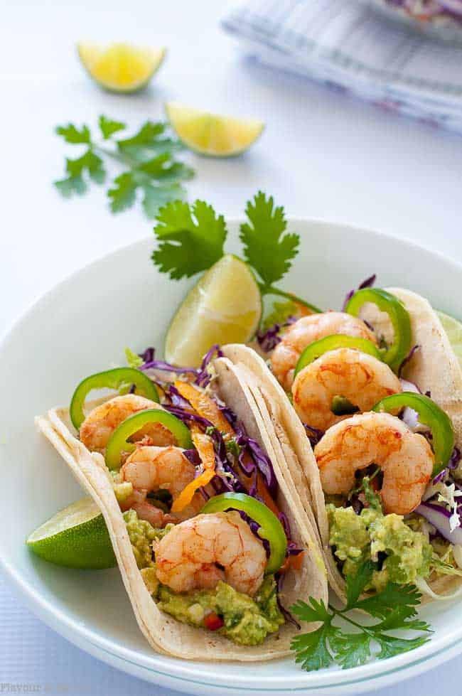These Shrimp Tacos are loaded with zesty Tomatillo Guacamole, Cilantro Lime Slaw and garlicky buttered shrimp. Top them off with fresh jalapeño slices and a squeeze of lime.