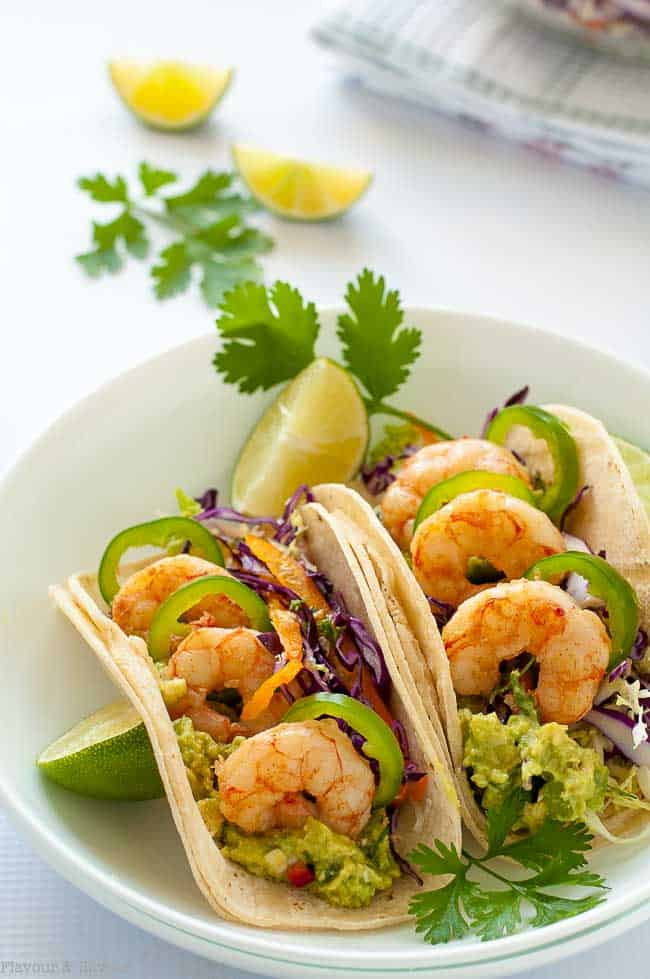 Shrimp Tacos with Cilantro Lime Slaw in a white bowl garnished with lime wedges and cilantro leaves