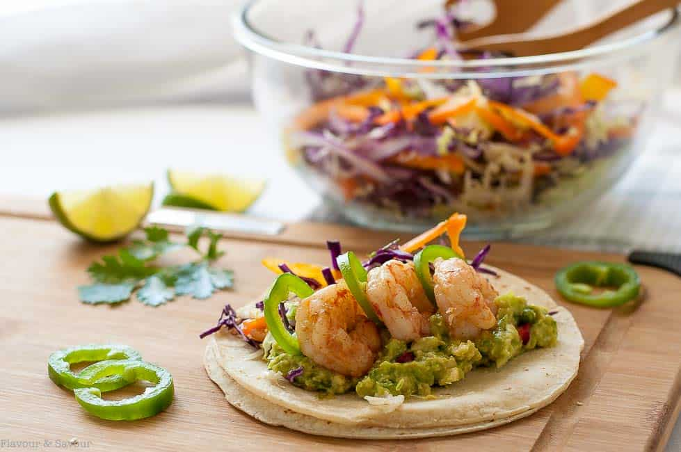 These Shrimp Tacos with Tomatillo Guacamole and crunchy Cilantro Lime Slaw. They're topped with garlicky buttered shrimp, fresh jalapeño and a squeeze of lime.