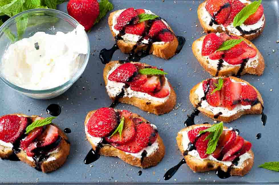 Strawberry Whipped Feta Crostini with Balsamic Drizzle on a baking sheet with a bowl of whipped feta |www.flavourandsavour.com