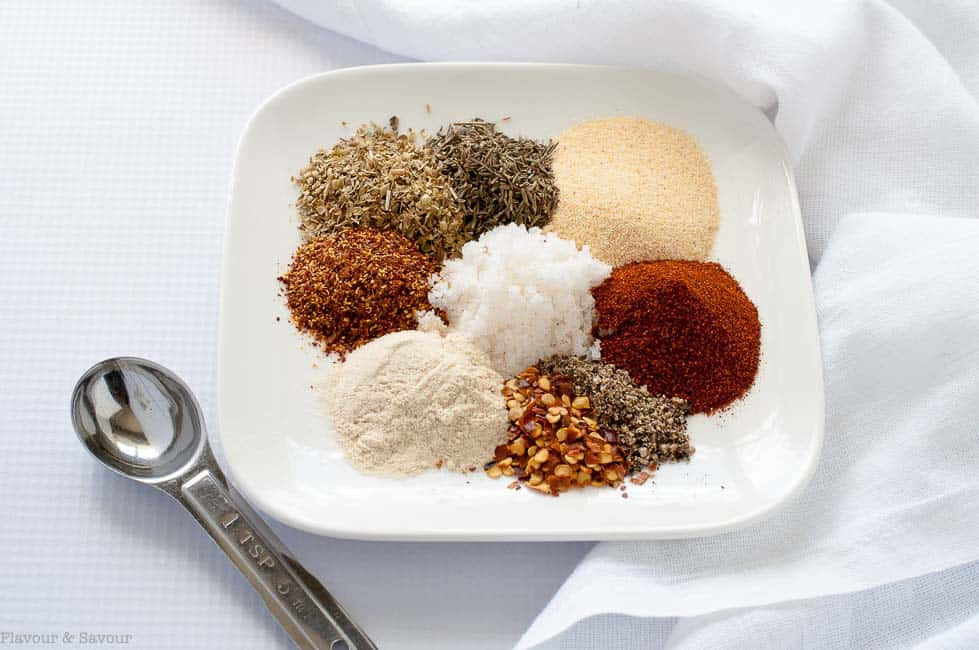 Cajun Seasoning Mix ingredients on a plate with a measuring spoon