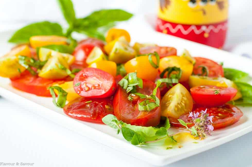 Close up view of Heirloom Tomato Salad with Basil, Capers and Feta on a white rectangular serving platter.