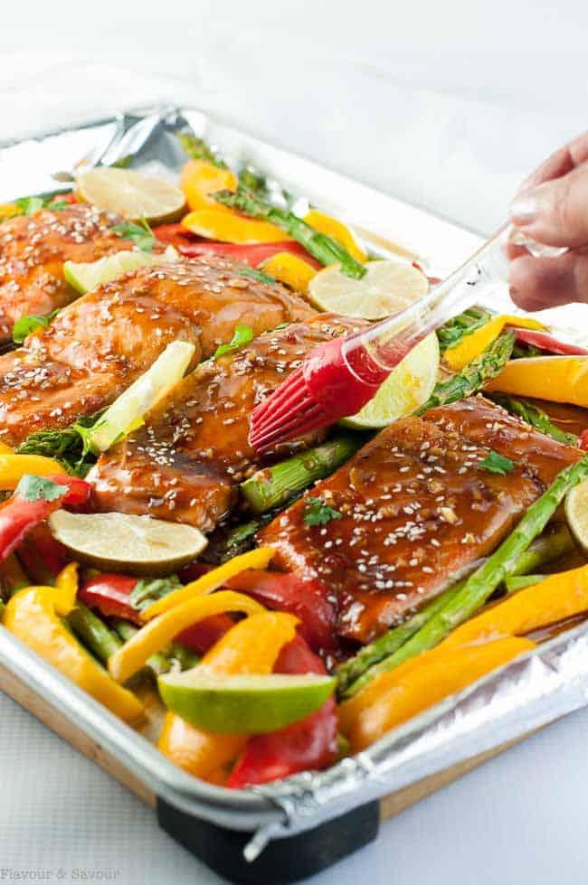 Brushing glaze on to salmon fillets to make Thai Chili Sheet Pan Salmon