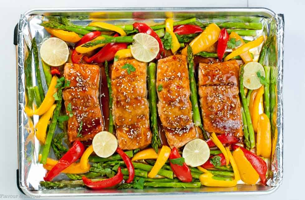 Thai Chili Salmon fillets surrounded by asparagus spears and red and yellow peppers on a sheet pan
