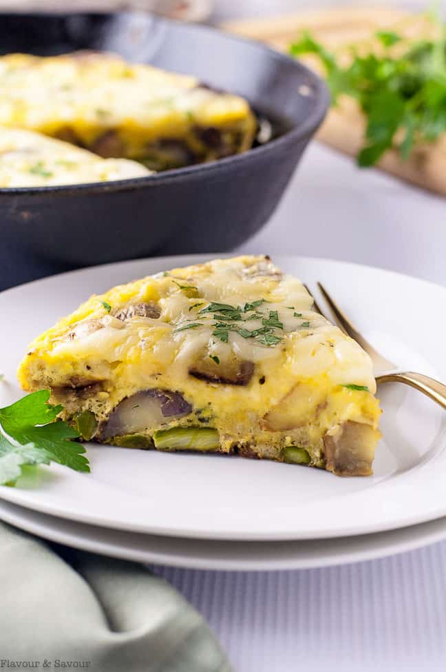 a wedge of Double Cheese Asparagus Leek Frittata on a white plate