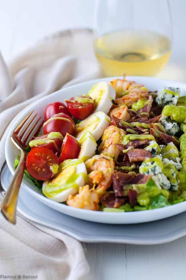 Lemon Garlic Shrimp Cobb Salad in a bowl with a fork and glass of wine.