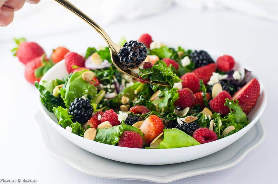 A forkful of Triple Berry Mixed Green Salad