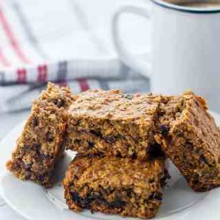 Chocolate Cherry Chia Oatmeal Bars on a plate with a cup of coffee