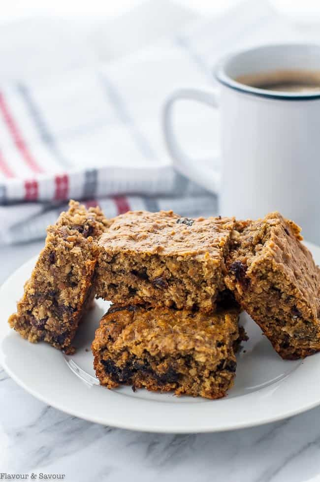 Gluten-Free Chocolate Cherry Chia Oatmeal Bars on a plate with a cup of coffee