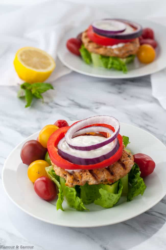 Two Open-Faced Harissa Chicken Burger on a wedge of lettuce garnished with red onion and red pepper rings and Greek Yogurt Sauce