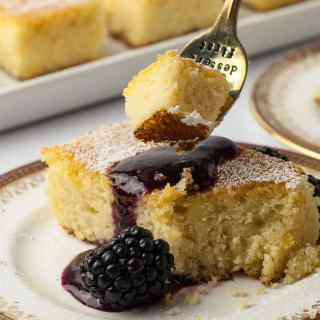 Close up view of a forkful of Flourless Lemon Almond Ricotta Cake with Blackberry Coulis