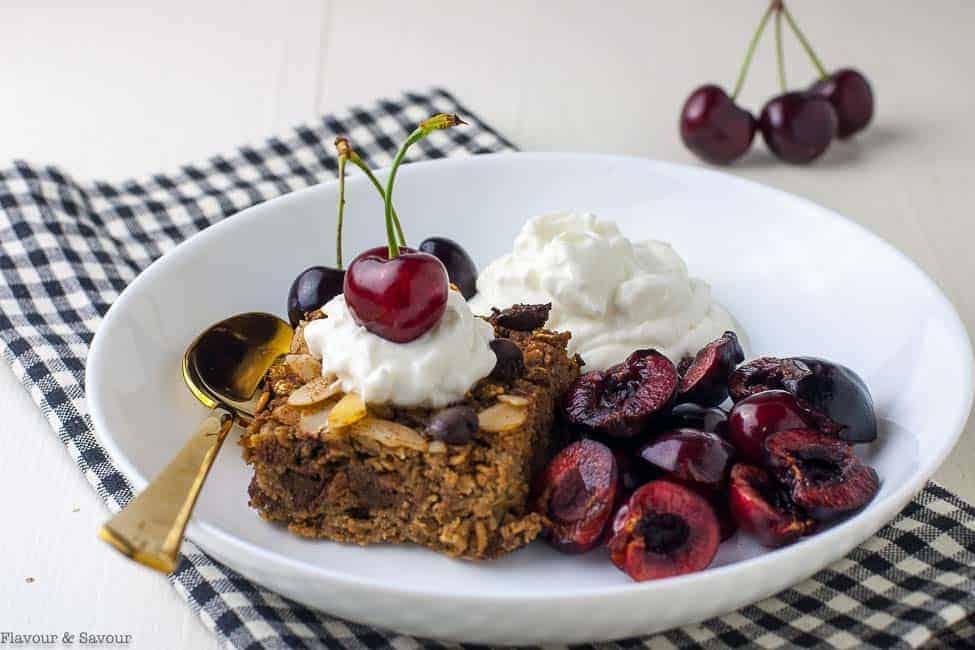 Chocolate Espresso Baked Oatmeal in a bowl with fresh cherries and Greek yogurt