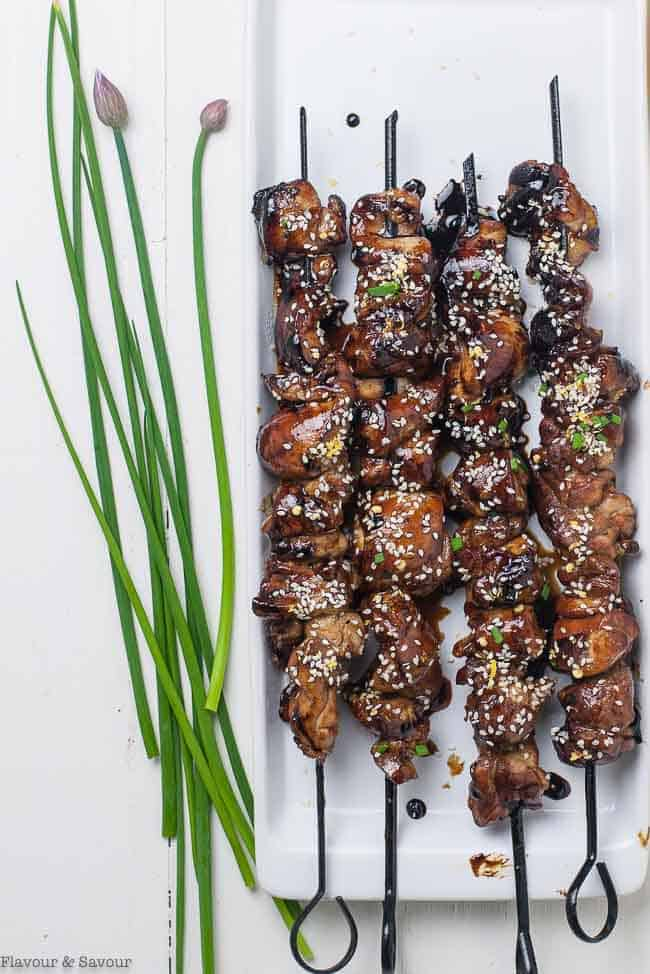Easy Japanese Chicken Yakitori Skewers on a white serving tray with fresh chives and chive blossoms