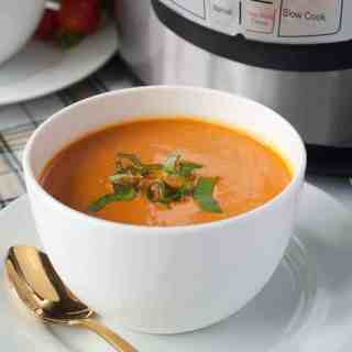 Wholesome Instant Pot Creamy Tomato Soup in bowls with Instant Pot in the background.