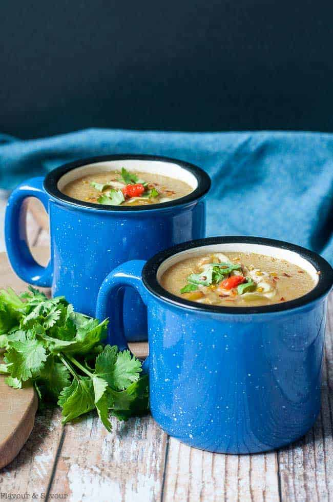 Two blue mugs of Slow Cooker Moroccan Harissa Cauliflower Soup