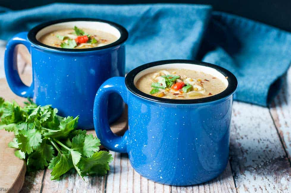 Two blue mugs of Slow Cooker Moroccan Harissa Cauliflower Soup with ciilantro