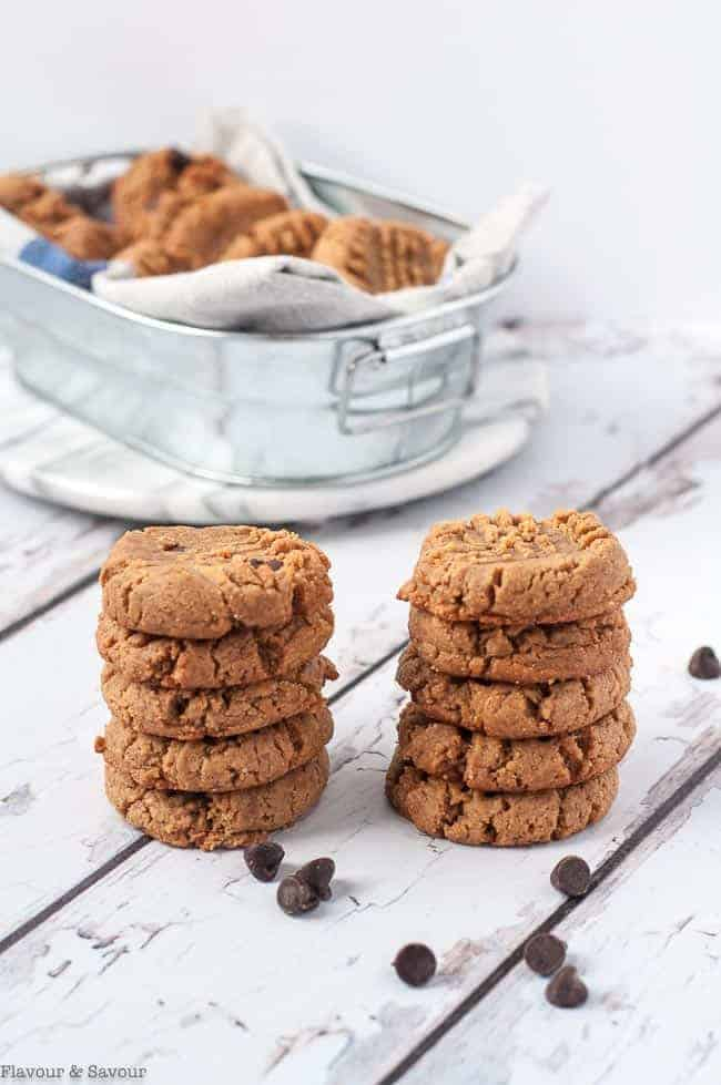 Two stacks of Easiest Ever 4-Ingredient Peanut Butter Cookies with metal basket of cookies