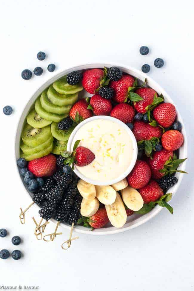 Creamy Lemon Curd Fruit Dip surrounded by berries and fruit