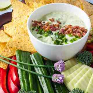 Close up view of cold jalapeno dip garnished with bacon crumbles and chive blossoms