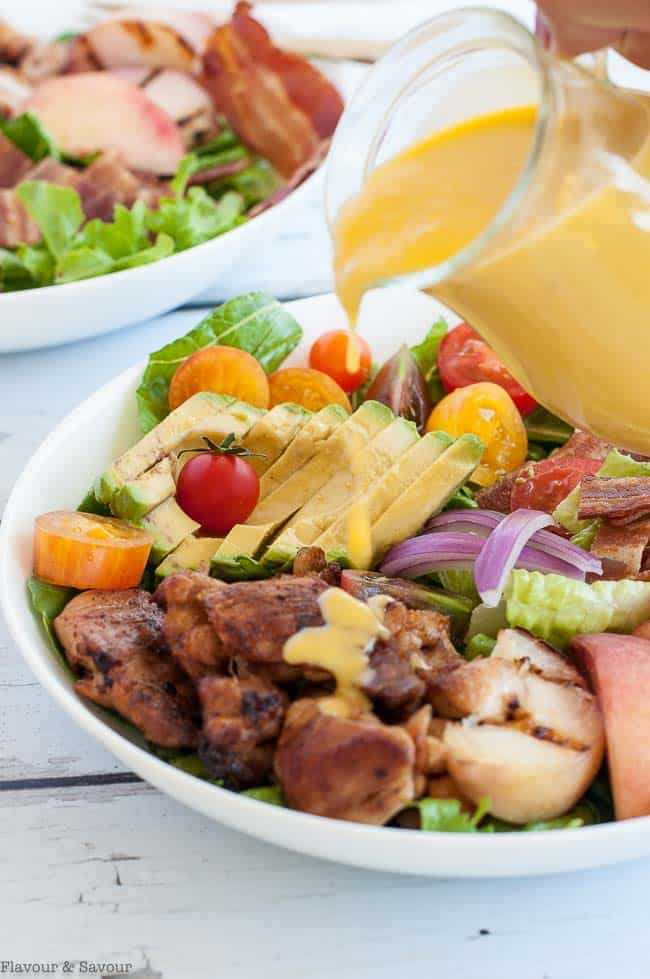 Pouring Peach Dressing on Chipotle Chicken Cobb Salad