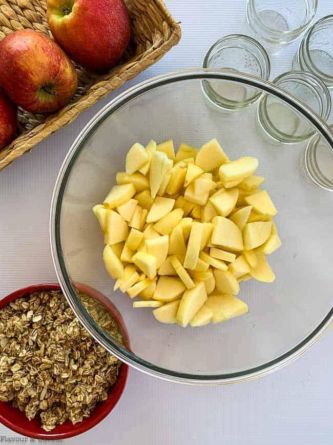 Sliced apples and crisp topping to prepare Apple Blackberry Crisp in Mason Jars.