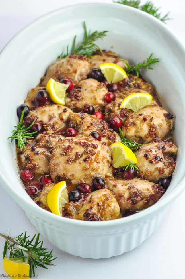 An oval baking dish with Cranberry Rosemary Boneless Chicken Thighs