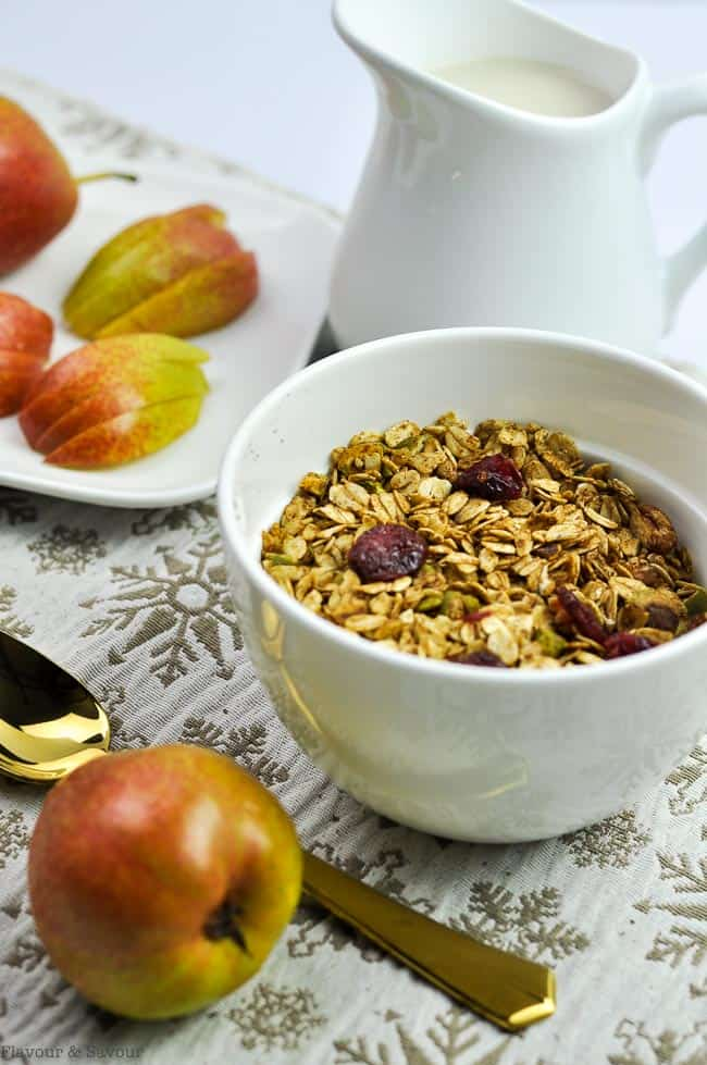 Homemade Gingerbread Granola in a bowl with sliced pears on a plate