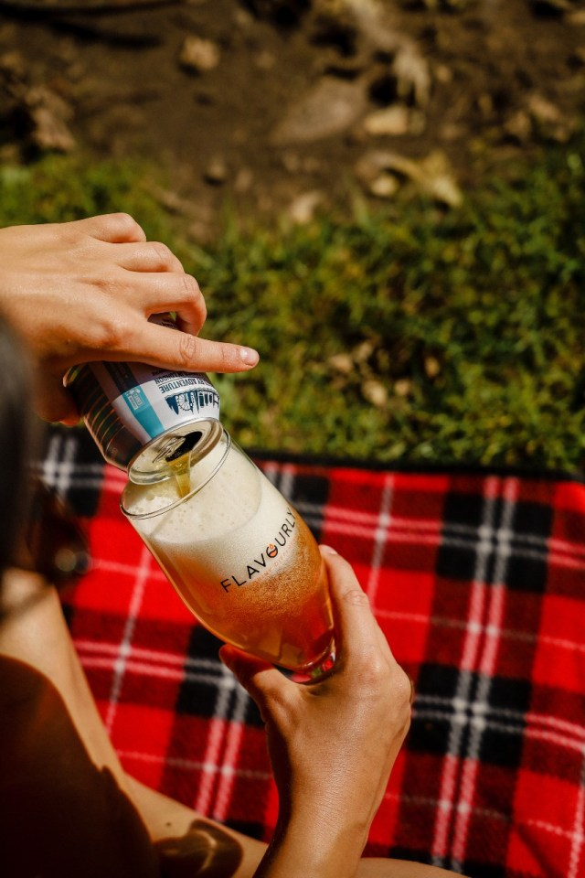 girl pouring beer in to a flavourly glass on a tartan rug