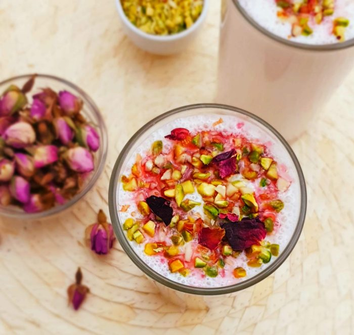 rose lassi in a glass with pistachios and rose petals as topping on wood colour placemat