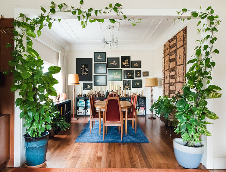 A dining room fueled by vintage collectibles, antique pictures, and maroon-plated furniture.