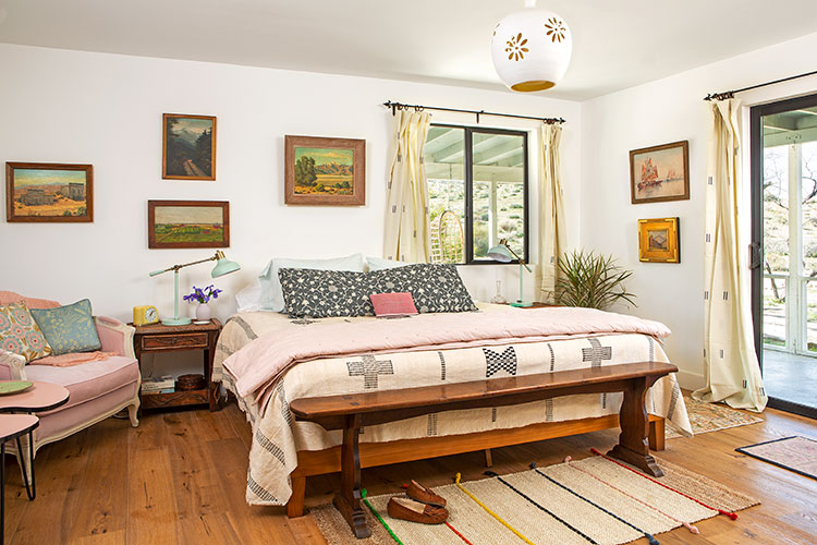 A moroccan-inspired renovation focused on a chic bed frame with pink sheets and reclaimed wood tabletop directly next to it.