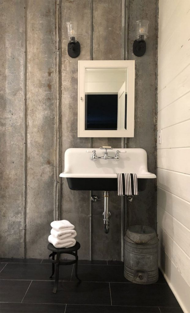 A bathroom, complete with a metal-based wall scheme, vintage milk stool, and white fixtures.